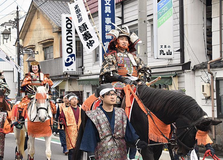 馬に乗り上丸子商店街を練り歩く木曽義仲役の談慶さん(右)と巴御前役の土屋さん