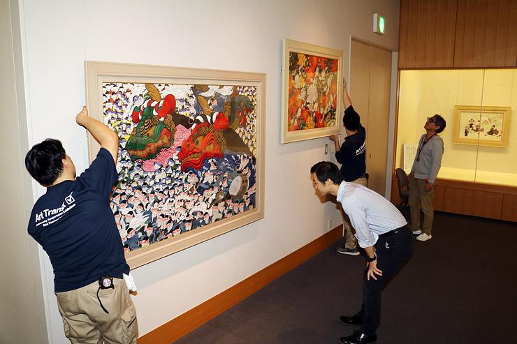 展示替えで「唐津くんち」(左)などを飾り付ける学芸員ら=県水墨美術館