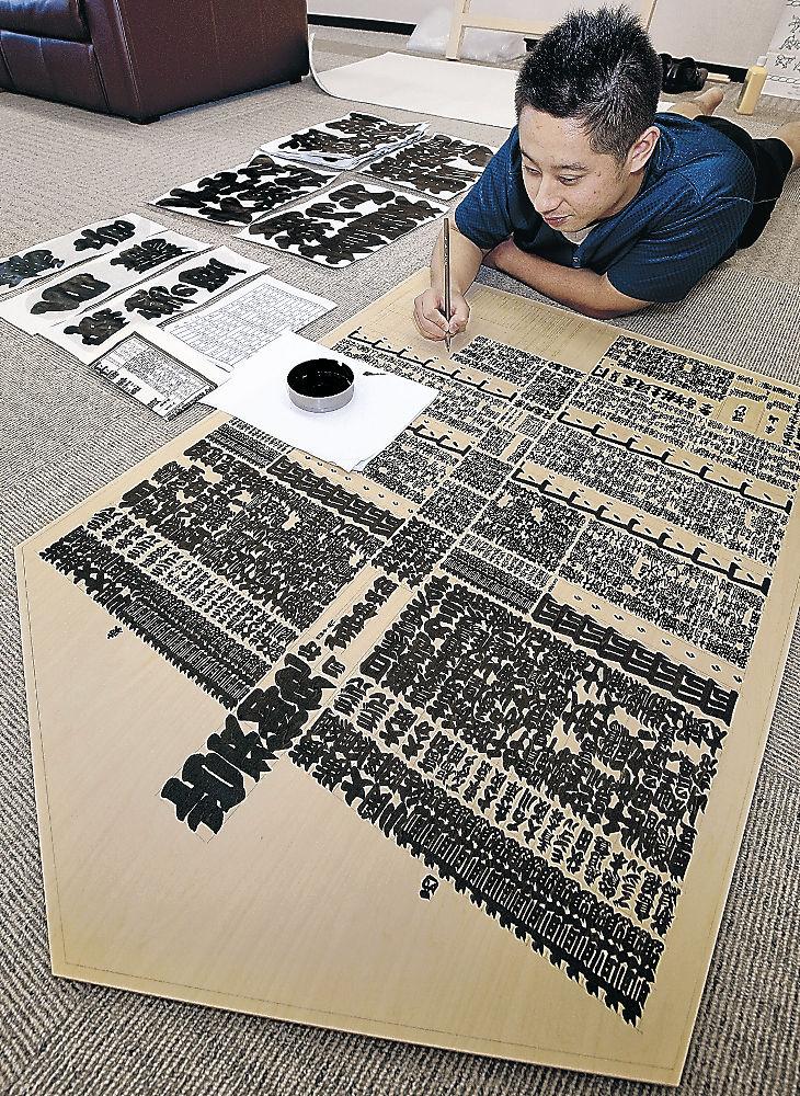 独特の相撲字で板番付を仕上げる行司の木村さん=北國新聞会館