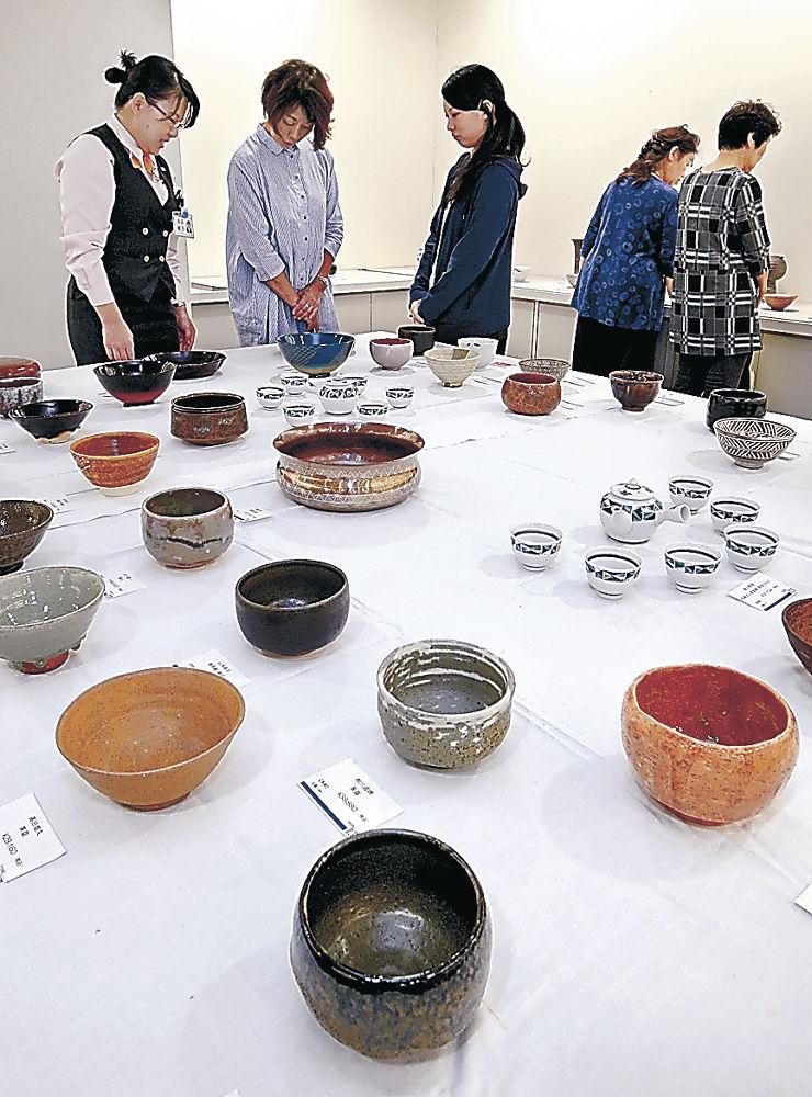 新作茶道具を品定めする来場者=金沢市のめいてつ・エムザ5階美術サロン