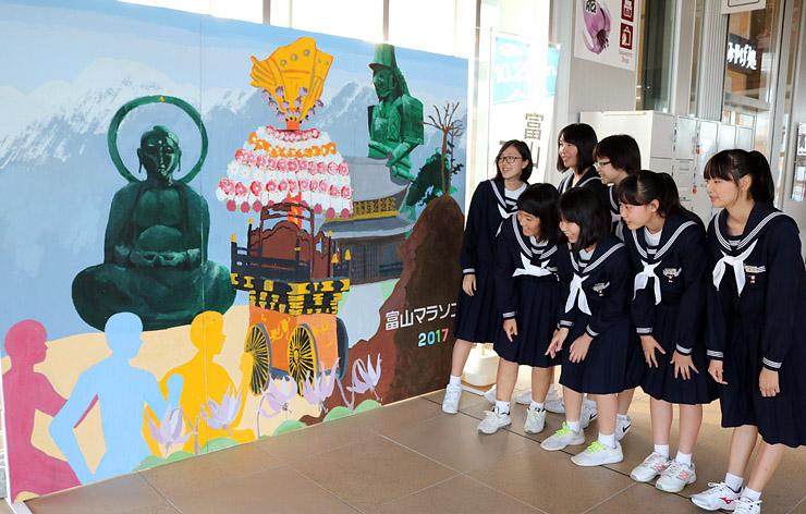 歓迎パネルの出来栄えを確認する生徒=JR新高岡駅