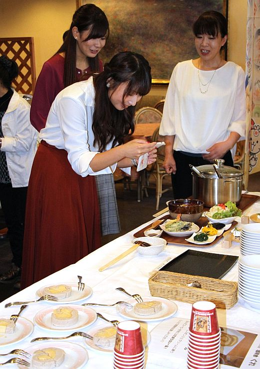 試食会でSNS用に米粉グルメの写真を撮る参加者=胎内市東本町