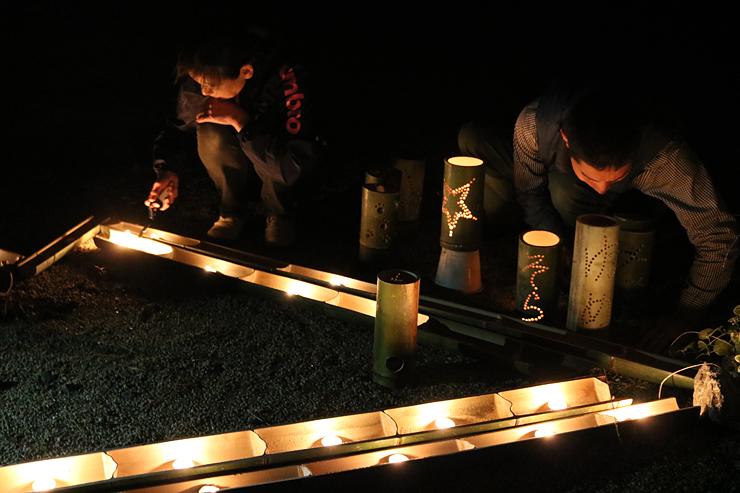 「森のいさり火」の竹灯籠に試験点灯する実行委関係者=氷見あいやまガーデン