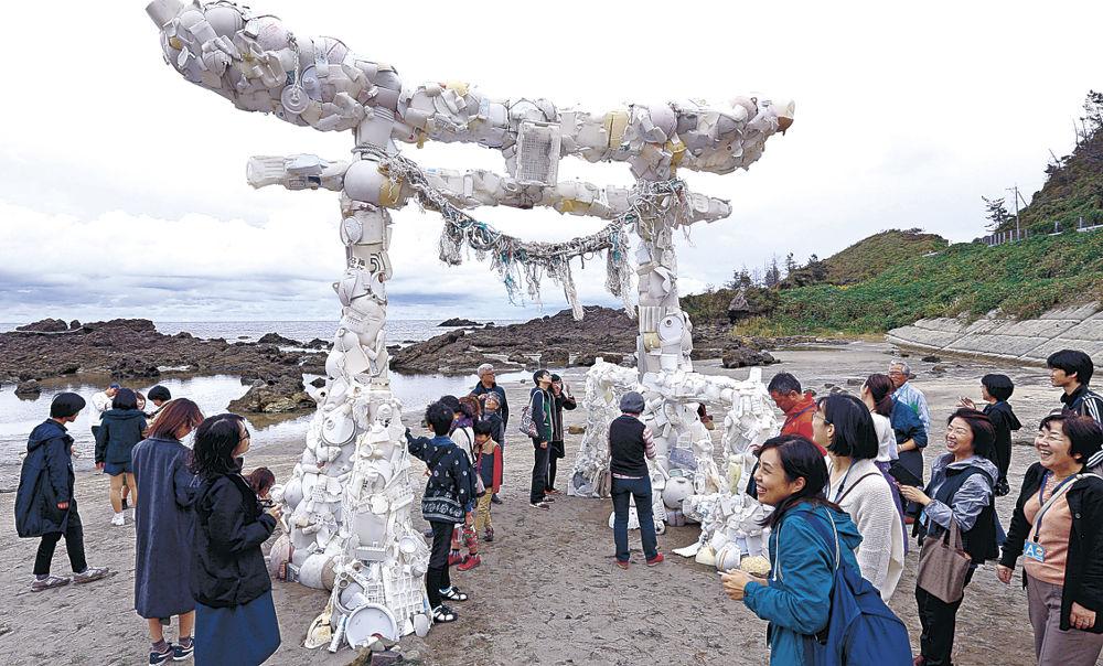 漂着物を鳥居の形に組み合わせたアート作品に見入る鑑賞者=珠洲市笹波町