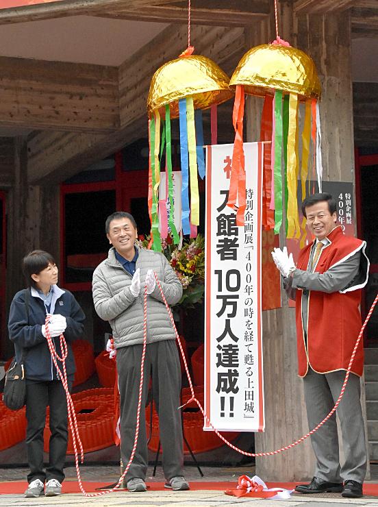 記念のくす玉を割った10万人目の入館者の持田夫妻(左の2人)と母袋市長