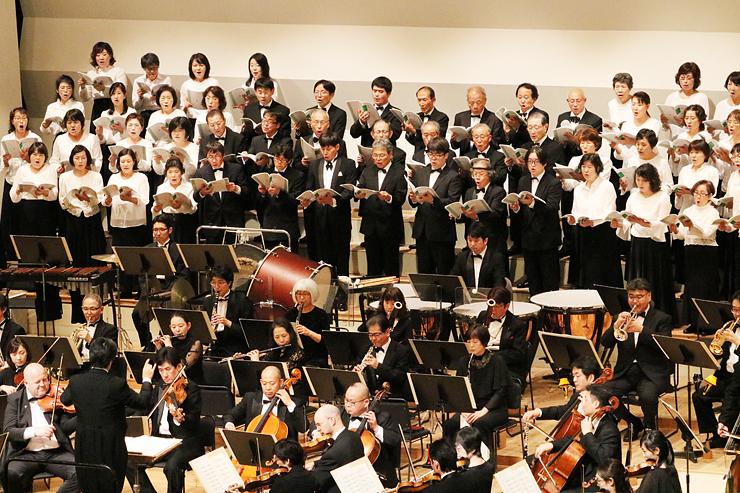 オーケストラ・アンサンブル金沢の演奏に合わせ、「大伴家持の三つの歌」を合唱する五環の森合唱団(奥)=高岡市民会館