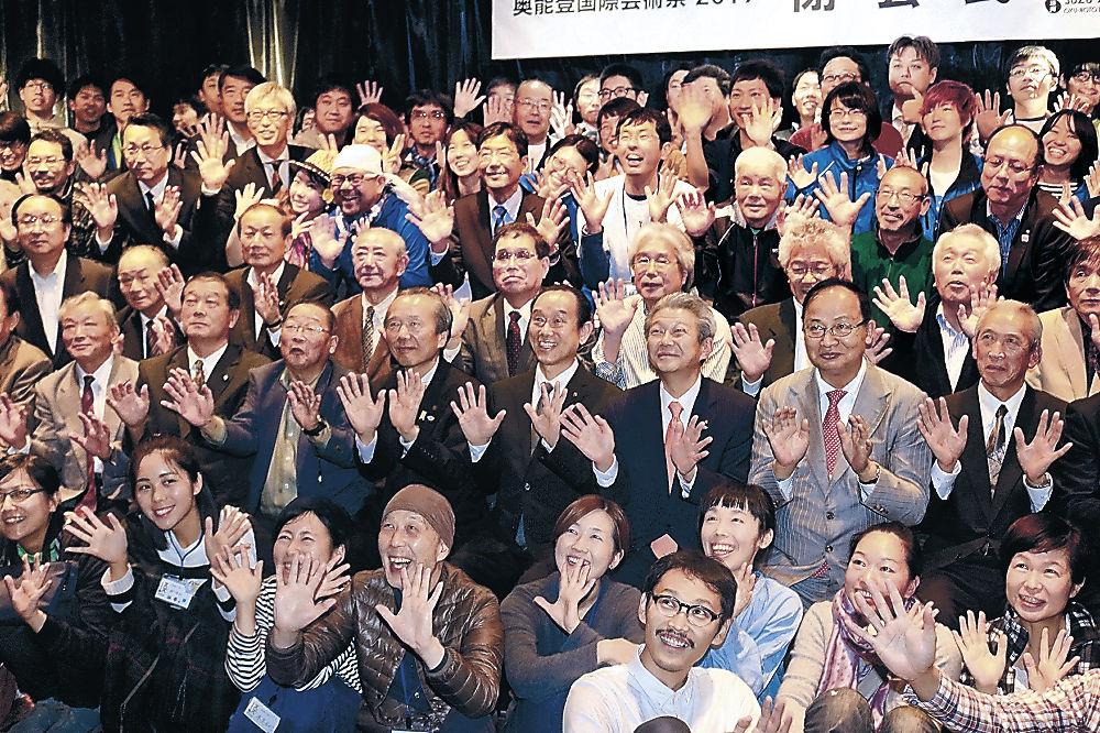 閉会式で記念写真に納まるサポーターや住民=珠洲市飯田町の「さいはてのキャバレー」