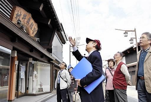 ガイドと福井県勝山市の中心部を巡る参加者=24日、同市本町2丁目