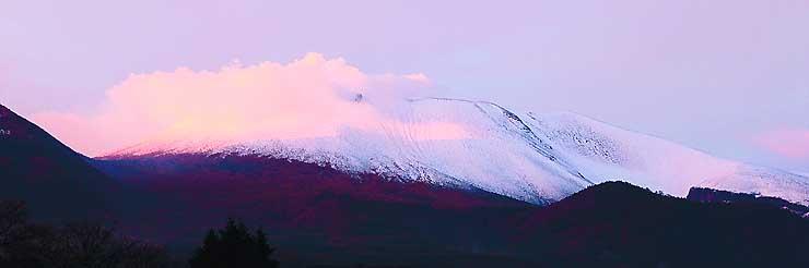 中腹まで白く染まり、夕焼けに照らされる浅間山=25日午後4時54分、御代田町塩野