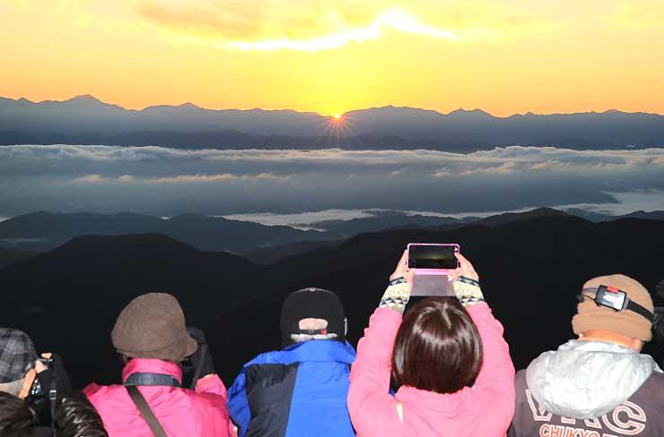 眼下に広がる雲海と、南アルプスの向こうから姿を見せた御来光を楽しむ観光客。幻想的な光景を写真に収めていた=26日午前6時9分、阿智村