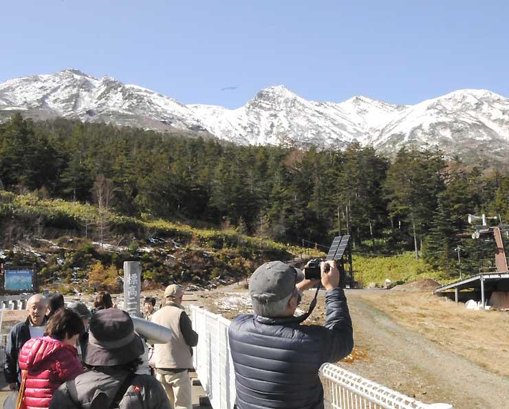 御岳ロープウェイの飯森高原駅で、冠雪した御嶽山を写真に収めたり、眺めたりする人たち