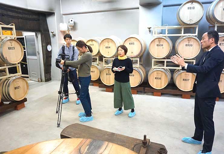井筒ワインで塚原専務(右)の説明を受けながら撮影するシンガポール国営放送の番組スタッフ