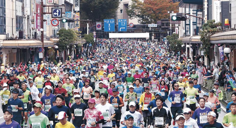 繁華街の大通りを埋め尽くして疾走するランナー=金沢市片町1丁目