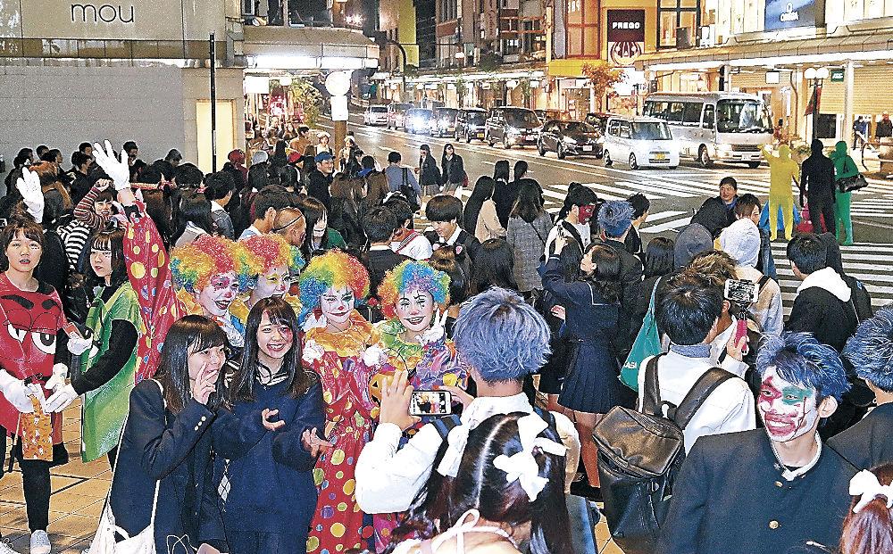思い思いの仮装を楽しむ若者らでにぎわう街中=31日午後8時半、金沢市片町2丁目
