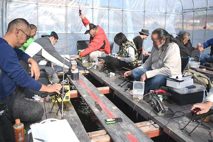 桟橋につないだドーム船から釣り糸を垂らし、ワカサギの当たりを待つ釣り客たち