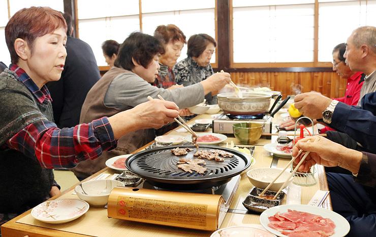 イノシシ肉を使った料理を試食する住民ら