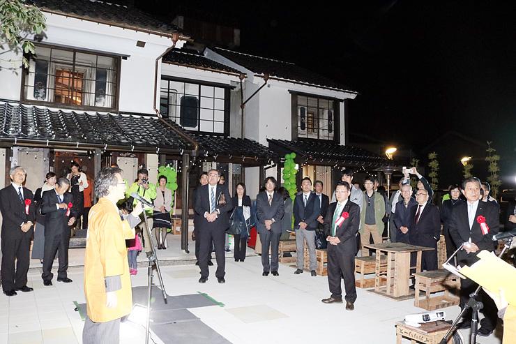 改修を終えた蔵の前であいさつする菅野社長(左)