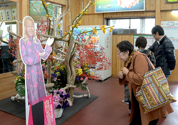 假屋崎さんの生け花を鑑賞するJR信濃大町駅の利用客ら