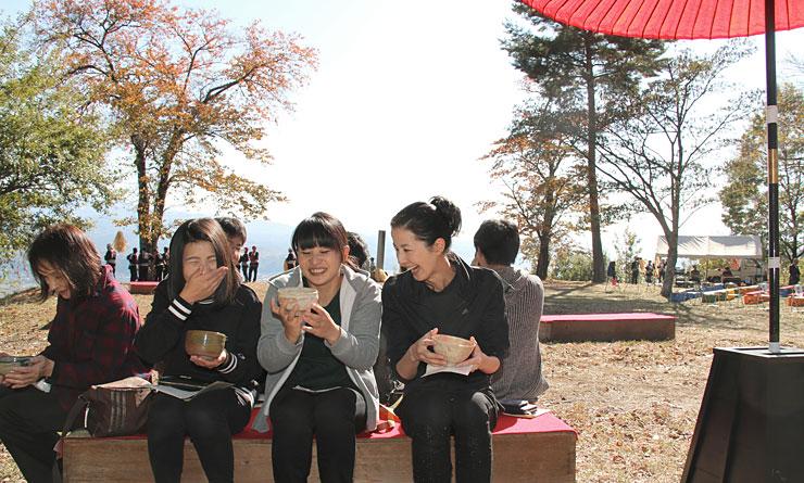 紅葉が進む松岡城址で野だてを楽しむ人たち。抹茶を飲み終わった後は「器も楽しまないとね」