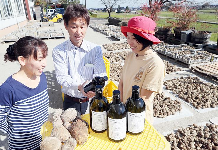 試作した里芋焼酎を手にする義浦代表(中央)