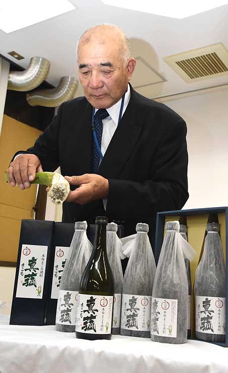 「黒穂菌」が付着したマコモタケを手に持ち、焼酎「真菰」をPRする中沢社長