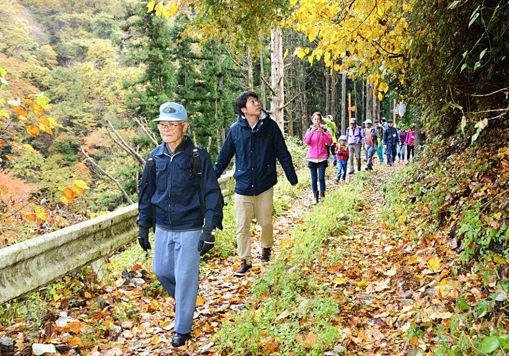 白沢さん(左)ら地元住民の案内で旧遠山森林鉄道の軌道跡を歩く参加者たち