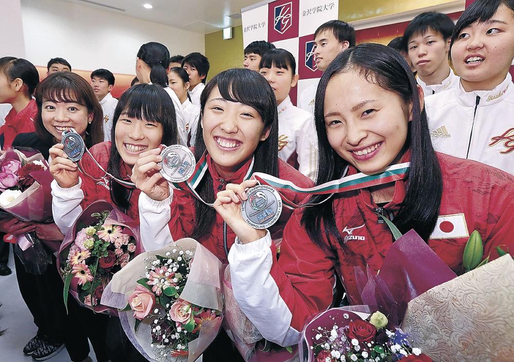 石川県に凱旋し、メダルを手に笑顔を見せる(右から)岸、森、高木の3選手と丸山本部長=14日午後5時半、小松空港