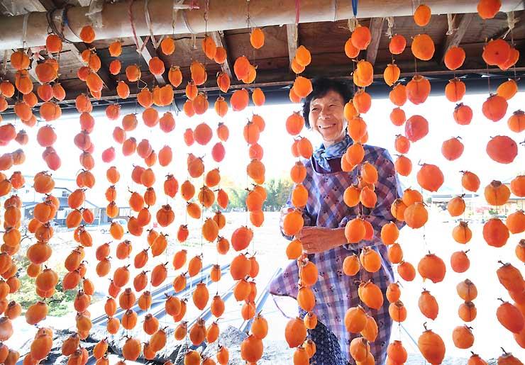屋根に上り、軒先で干し柿作りに精を出す原秀子さん