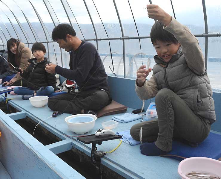 ドーム船でワカサギ釣りを楽しむ家族ら