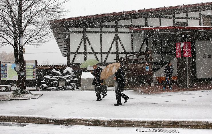 雪が降りしきる中、傘を差して歩く人たち=16日午前9時5分ごろ、立山駅