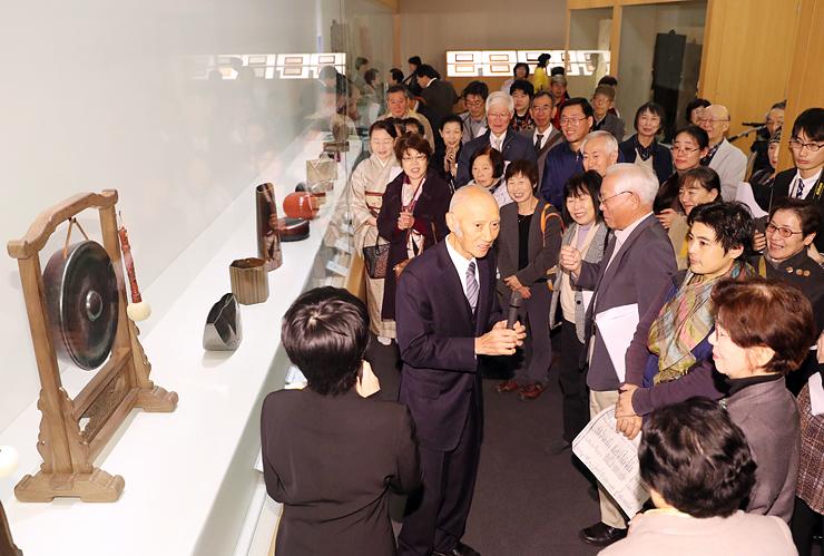 「日本のわざと美」展の会場で、大澤さん(中央)の説明を聞きながら、作品を鑑賞する来場者=県水墨美術館