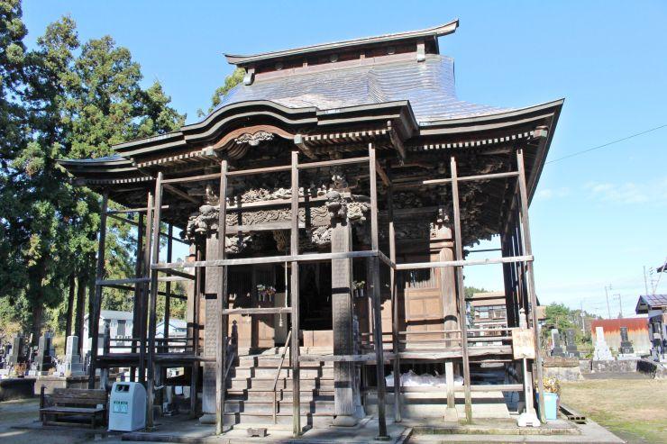 軒を支える部分に鳥や獣の彫刻が施されている潮音寺観音堂=小千谷市小粟田