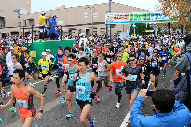 勢いよくスタートするハーフマラソンの出場者=砺波チューリップ公園前