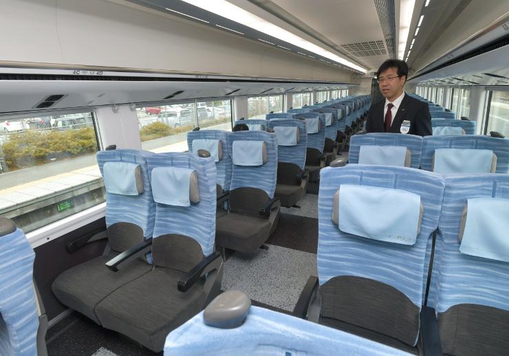 水色を基調にデザインされた新型車両の普通車の座席。可動式の枕を採用した