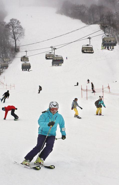 新潟県内トップを切ってオープンしたかぐらスキー場で初滑りを楽しむ来場者=23日、湯沢町三俣