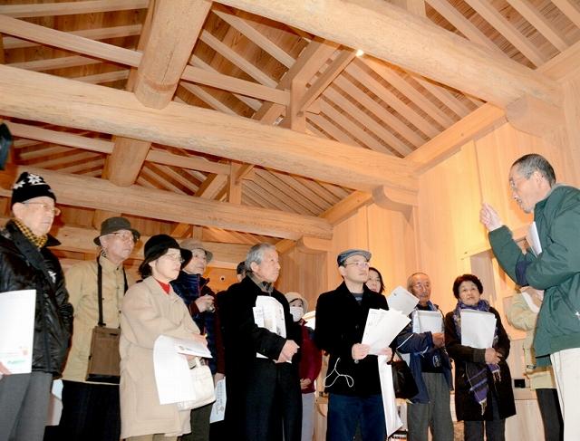 山里口御門の復元工事について設計を担当した国京さん(右)の解説を聞く内覧会参加者=25日、福井市大手3丁目