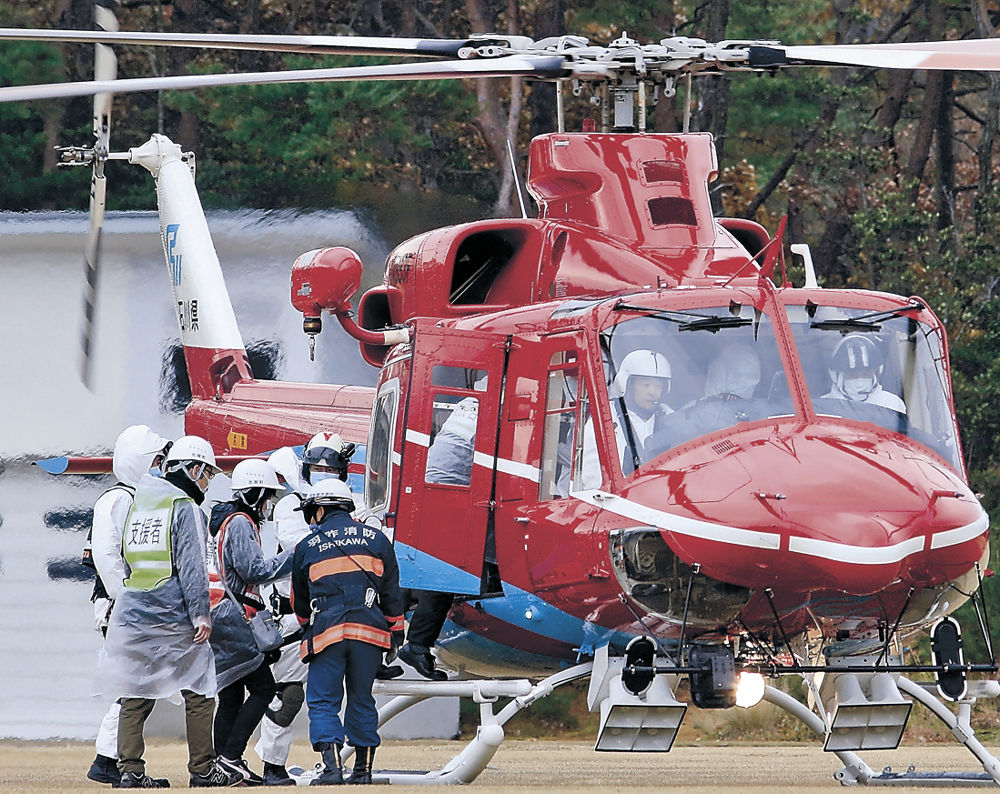 原子力防災訓練で石川県消防防災ヘリ「はくさん」に乗り込み、避難する住民=26日午前10時48分、志賀町陸上競技場