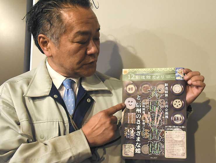 昆虫食を紹介する企画展のチラシを手にする捧館長