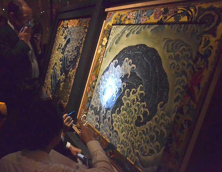 北斎館に返却された怒濤図の女浪(手前)の状態などを見る浅野館長(左)ら