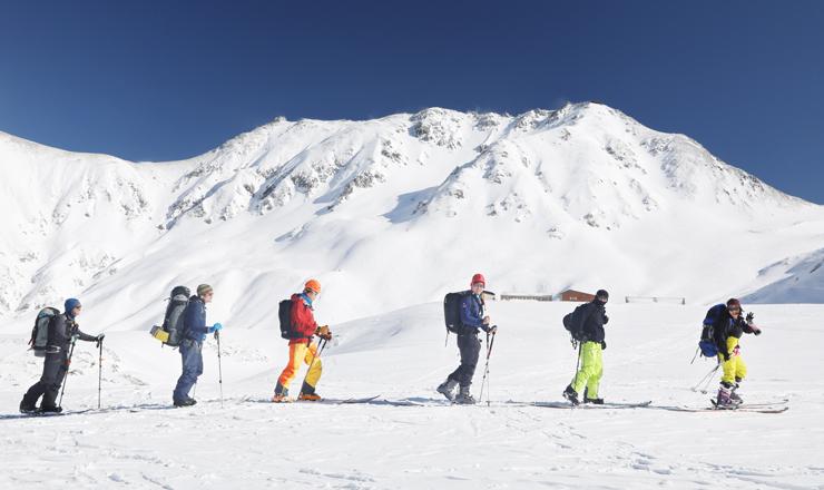 雄山(右奥)など立山連峰の景色を眺めながらスキーを楽しむ人たち=立山・室堂(写真部部長デスク・垣地信治)