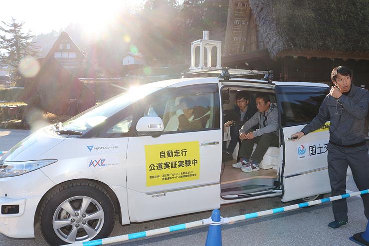 観光客が乗り込み、出発する自動運転車両 =相倉合掌造り集落