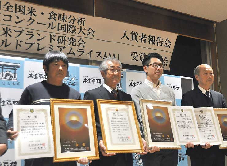 「ゴールドプレミアムライスAAA」に認定され、他のコメ生産農家と記念撮影に納まる木島平米ブランド研究会長の嘉部さん(左から2人目)