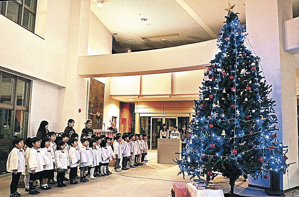 点灯したツリーの前で賛美歌を披露する園児=金沢市の北陸学院大国際交流研修センター