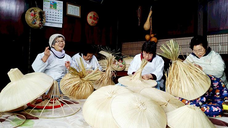 伝統の技術で菅笠を作る人々=高岡市福岡地域