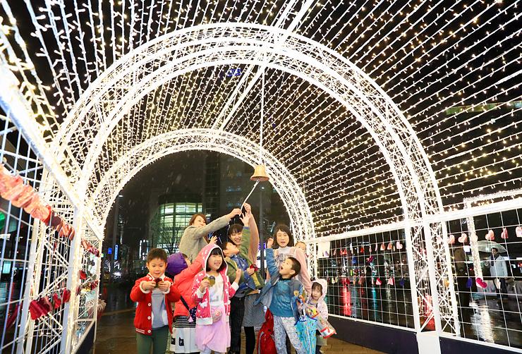イルミネーションゲートの「幸せのベル」を鳴らす園児たち=富山駅南口前広場