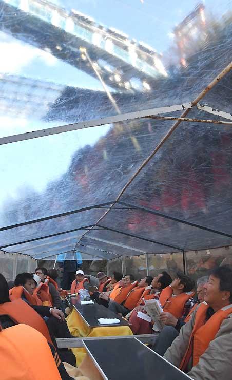 建設中の「天龍峡大橋」を見上げる観光客ら。こたつで暖を取りながら天竜川を下った