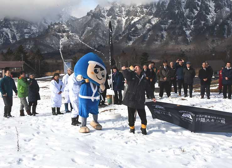「雪ごい祭り」で種池からくんだ水を戸隠スキー場にまく参加者ら