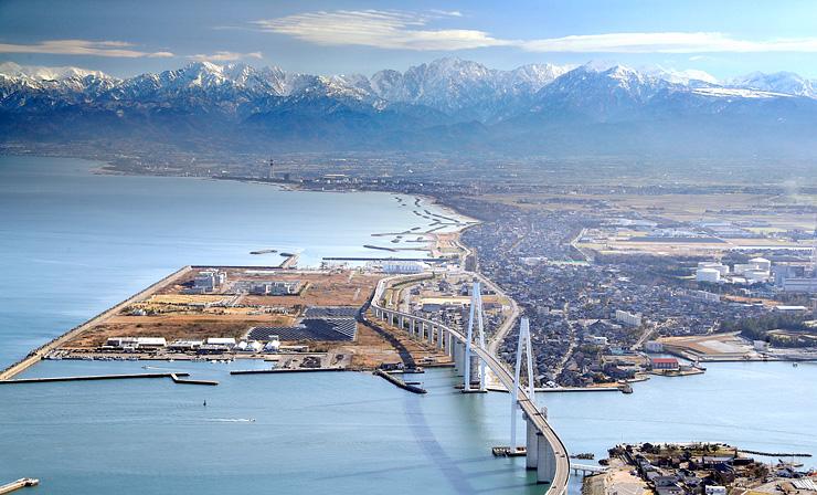 2本の主塔が空に伸びる新湊大橋(手前)の奥にくっきりと姿を現した立山連峰=3日午前10時50分ごろ、富山新港上空の本社チャーターヘリから