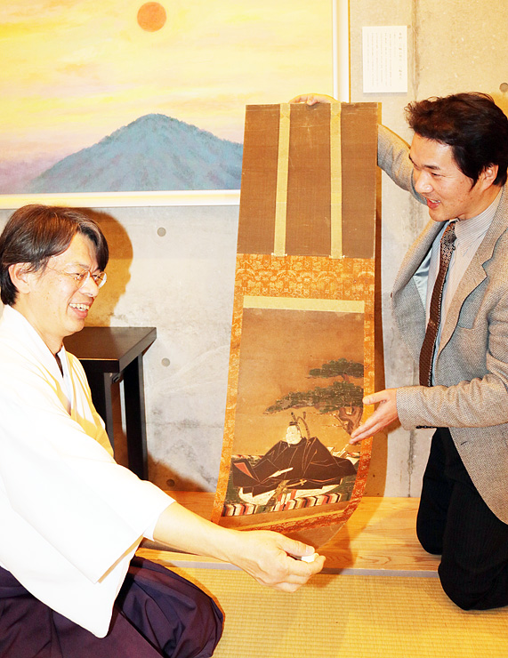 修復が完了した掛け軸を眺める舩木宮司(左)と岩崎さん