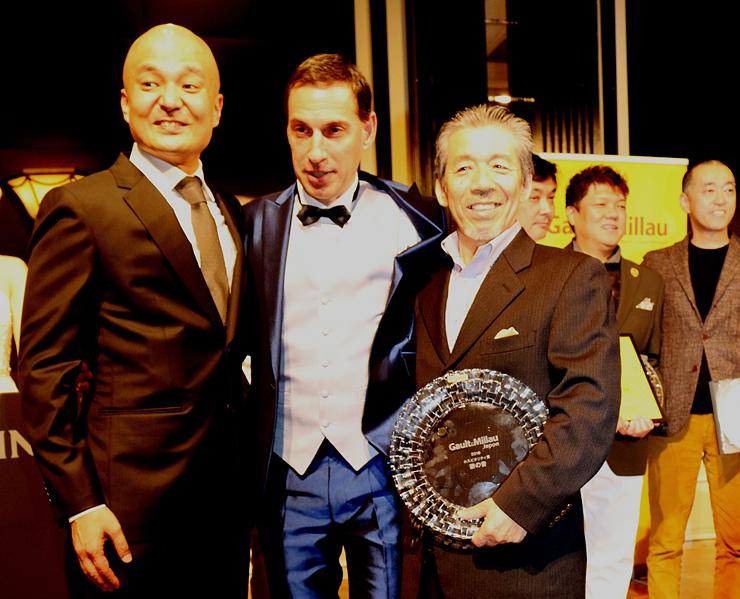 ホスピタリティ賞を受賞し、「ゴ・エ・ミヨ」日本版第2号に掲載された「薪の音」館主の山本さん(手前右)=東京都内のホテル